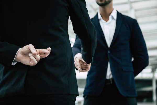 Business man crosses his fingers behind his back while shaking another business man's hands.